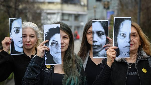 Women's rights activists hold printed half face pictures showing victims of domestic violence during a protest in Bucharest on March 4, 2020