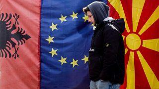 Makedonya'nın başkenti Üsküp'te Arnavutluk, Kuzey Makedonya ve AB bayraklarının önünde yürüyen bir kişi