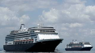 The Zaandam cruise ship, left, carrying some guests with flu-like symptoms, is anchored shortly after it arrived to the bay of Panama City, Friday, March 27, 2020.