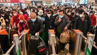 A többi között Vuhanba induló utasok tolonganak a sanghaji pályaudvaron