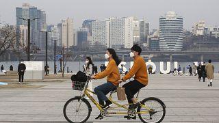 Güney Kore'nin başkenti Seul'de bisiklet süren bir çift, koronavirüsten korunmak için maske taktı