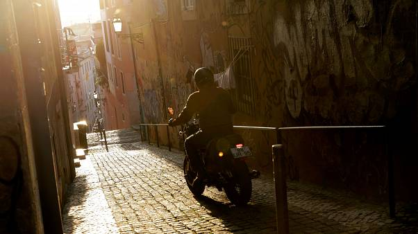 A man rides his motorbike in Lisbon