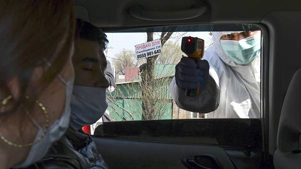 عامل في قطاع الصحة يقيس درجة حرارة راكبي سيارة عند حاجز في بيشكبك عاصمة قرغيزستان - 2020/03/25