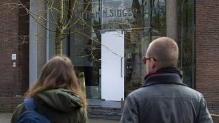 Two people look at the glass door which was smashed during a break-in at the Singer Museum in Laren, Netherlands, Monday March 30, 2020.