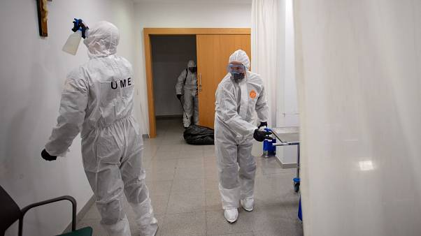 A member of the Military Emergencies Unit (UME) sprays a crucifix as they carry out a general disinfection at the Sant Antoni care facility in Barcelona on March 27, 2020.