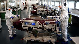 Du personnel soignant en train de mettre en place une unité où seront accueillis des patients atteints du Covid-19 dans l'hôpital de Verduno, nord de l'Italie, le 29/03/2020.