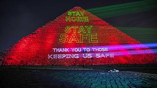 Messages of support for health workers are displayed on a pyramid in Egypt