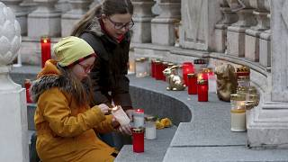 Two girls light candles in front of the plague column in Vienna, Austria, Thursday, March 26, 2020.