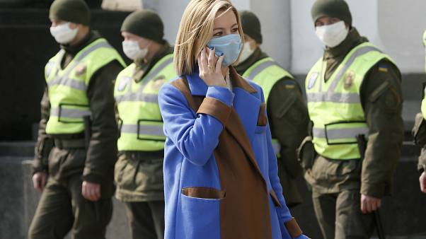A woman wearing a face mask to protect against the coronavirus talks on her cell phone, with masked National Guard soldiers in the background, as she approaches the parliament
