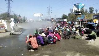 السلطات الهندية ترش مجموهة من العمال المهاجرين بسائل تعقيم