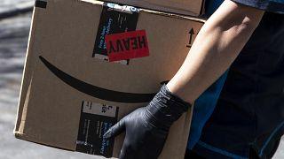 Csomagot visz házhoz az Amazon internetes kereskedelmi cég egyik kiszállítója Los Angelesben 2020. március 26-én.