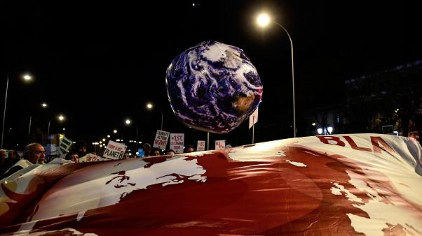 A balloon in the shape of the Earth is pictured during a mass climate protest during the COP25 summit in Madrid, December 6, 2019. (Photo by CRISTINA QUICLER / AFP)