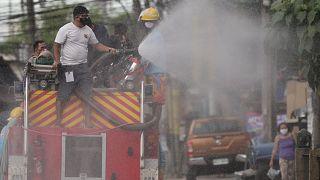 Filipinlerin başkenti Manila'da bir görevli, koronavirüsün yayılmasını önlemek amacıyla caddede dezenfekte çalışması yaparken