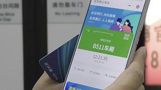 رمز أخضر يظهر على الهاتف المحمول لمواطن صيني في مترو الأنفاق  بمدينة ووهان