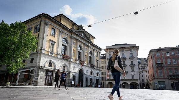 People walk in Riforma's square on May 7, 2019 in Lugano, southern Switzerland. (Photo by Fabrice COFFRINI / AFP)