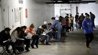 In this March 13, 2020 file photo, unionised hospitality workers wait in line in a basement garage to apply for unemployment benefits in Los Angeles
