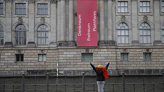 A woman stretches at the river Spree on the other side of the Bode museum at the Museum island in Berlin, on April 2, 2020. (Photo by Odd ANDERSEN / AFP)