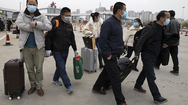 صينيون يحملون حقائبهم متوجيهن إلى مدينة ووهان وسط البلاد