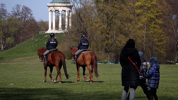 عناصر شرطة يراقبون تطبيق التباعد الاجتماعي في الحديقة الإنكليزية بمدينة ميونخ بألمانيا