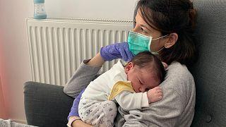 Venssa Muro eldiven ve maske ile bebeğine sarılıyor