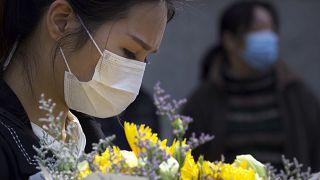امرأة تحمل الزهور تكريما لضحايا الوباء في ووهان - 2020/04/04