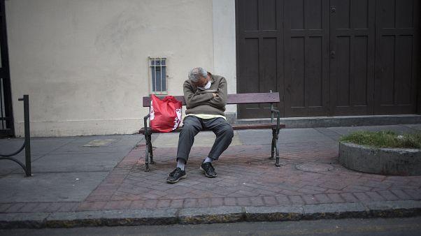 رجل يجلس على مقعد خشبي في العاصمة ليما - 2020/04/03