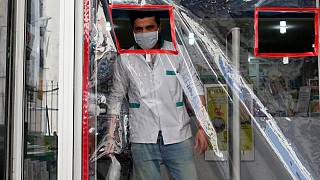 صيدلي يرتدي كمامة قرب باب مغطى بالبلاستيك لتجنب العدوى في الدار البيضاء 27 مارس 2020