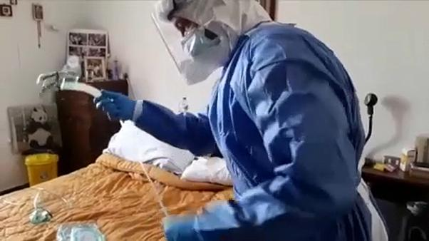 Doctor treating Italian women with coronavirus symptoms at home in Piacenza, Italy