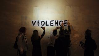 """A group of women paste the word """"violence"""" onto a street wall, part of a protest to draw attention to domestic violence, Paris, France, October 2019."""