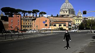 A woman walks with St Peter's Basilica in the background in Rome on April 6, 2020