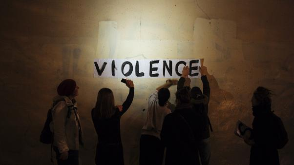 "A group of women paste the word ""violence"" onto a street wall, part of a protest to draw attention to domestic violence, Paris, France, October 2019."