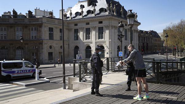 Полицейский проверяет у жителя Парижа разрешение на выход из дома.
