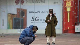 Dos personas mirando sus teléfonos en Pekín frente a una publicidad de 5G