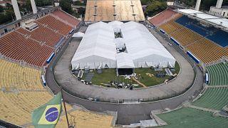 Des travailleurs ont mis en place un hôpital de campagne temporaire pour traiter les patients atteints de COVID-19 à l'intérieur du stade Pacaembu à Sao Paulo, au Brésil.