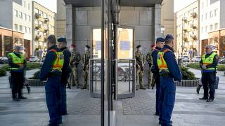 Hungarian policemen and soldiers stand guard at an entrance to the Great Market of Debrecen, Hungary