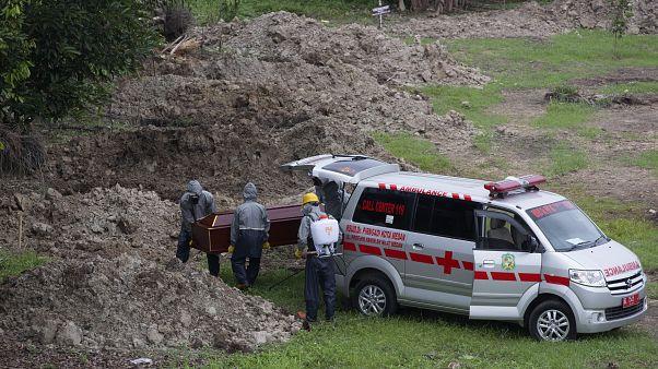 فرق طبية خاصة تقوم بدفن أحد الذين قضوا جراء الإصابة بفيروس كورونا المستجد في منطقة ميدان شمال سومطرة