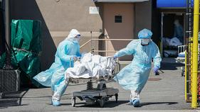Bodies are moved to a refrigeration truck serving as a temporary morgue at Wyckoff Hospital in the Borough of Brooklyn on April 6, 2020 in New York.