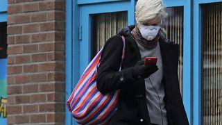 Une femme porte un masque et consulte son téléphone, le mardi 24 mars 2020, dans le quartier de Capitol Hill à Seattle.