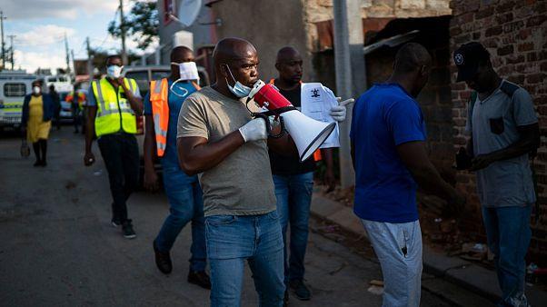 Ativistas comunitários e polícia verificam confinamento anti-Covid-19 na África do Sul