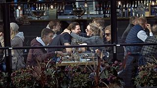 A couple hug and laugh as they have lunch in a restaurant in Stockholm, Sweden, Saturday, April 4, 2020