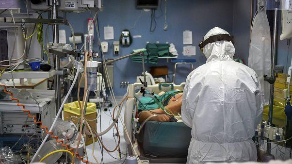 طبيب يعاين مريض مصاب بفيروس كورونا في قسم العناية المركزة لمشفى باسيني قرب ميلانو شمال إيطاليا