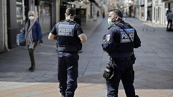 Local police patrol as pedestrians wear face masks in the main street of Sceaux, south of Paris,  on April 8, 2020