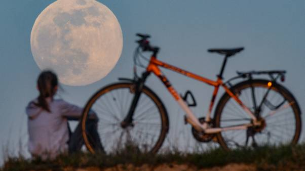 A cyclist stops to watch the Supermoon come up in Sieversdorf, eastern Germany on April 7, 2020. (Photo by Patrick Pleul / dpa / AFP) / Germany OUT