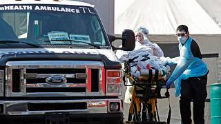 A patient is wheeled to an ambulance in New York