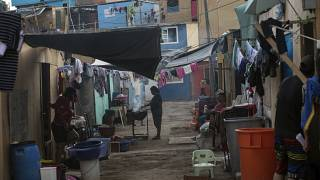 A woman cooks outside her house in a shanty town of Lima, Peru, Thursday, April 2, 2020. The country has ordered a lockdown amid a state of emergency due to the coronavirus..