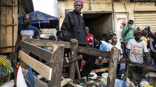 A shopkeeper watches as a bulldozer demolishes informal shops in an effort to stop the spread of the coronavirus, Dakar, Senegal, March 22, 2020.