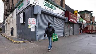 April 3, 2020: a woman walks by local stores during the coronavirus pandemic in New York.