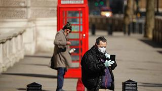 A man wearing a mask looks at his phone near Parliament Square, in London, Wednesday, March 25, 2020.