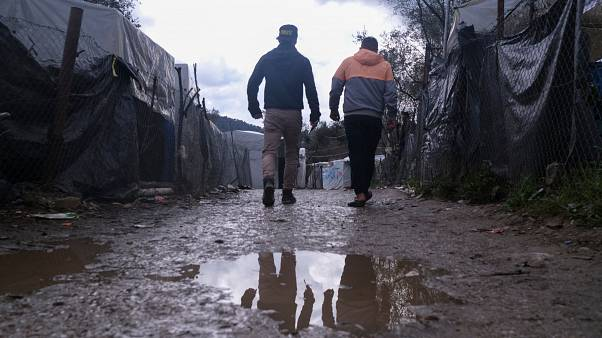 Migrants walk past makeshift tents outside the perimeter of Moria refugee camp
