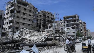 In this Monday, April 16, 2018 file photo, people stand in front of damaged buildings, in the town of Douma, the site of a suspected chemical weapons attack.